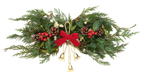 Christmas floral decoration with gold bells, red bow, holly, mistletoe, ivy, pinecones and winter greenery over white background  photo
