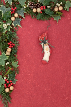 Christmas eve floral border with retro stocking bauble, holly, mistletoe, ivy and cedar leaf sprigs  over red mottled background  photo