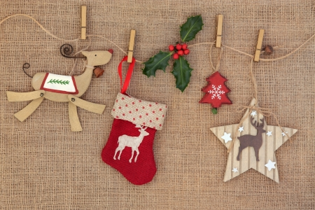 Old fashioned christmas decorations hanging on a line with holly over hessian background