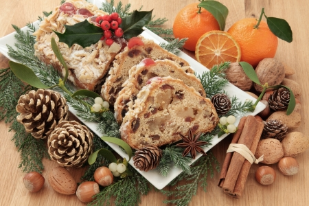 fruitcake: Stollen christmas cake with holly, mandarin oranges, nuts, spice and winter greenery over oak background  Stock Photo