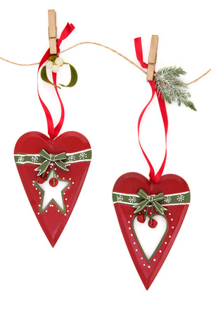 old fashioned christmas: Old fashioned christmas red heart bauble decorations with mistletoe and fir on a string line over white background  Stock Photo