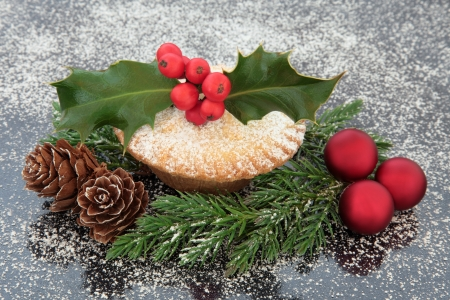 mince pie: Mince pie with holly and red berry leaf sprig, christmas baubles, fir and pine cones  Stock Photo