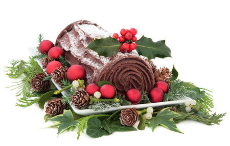 yule: Christmas chocolate yule log cake with red baubles and holly over white background