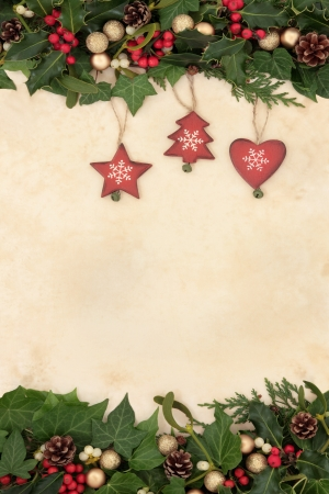 Christmas floral background border with wooden and gold bauble decorations, holly, ivy and mistletoe on old parchment paper  photo