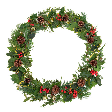 muerdago: Natural guirnalda de la Navidad con el acebo, el mu�rdago, hiedra, pi�as de pino y ramitas de hojas de cedro sobre fondo blanco Foto de archivo