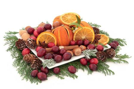 muerdago: Arándano Navidad y fruta seca de naranja con frutos secos, especias y el invierno verde sobre fondo blanco Foto de archivo