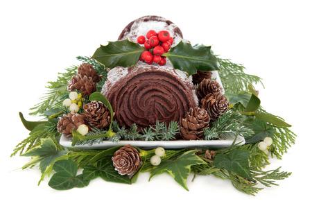 yule: Christmas chocolate yule log cake with holly, mistletoe and winter greenery over white background   Stock Photo