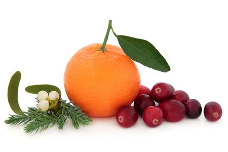 cranberry: Cranberry and mandarin orange fruit with mistletoe and winter greenery over white background  Stock Photo