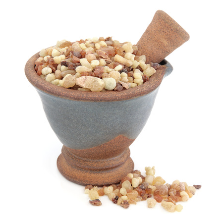 Frankincense and myrrh in a mortar with pestle over white background