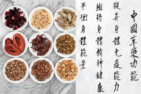 Traditional chinese herbal medicine with mandarin script calligraphy on rice paper over marble  Translation describes the functions to increase the bodys ability to maintain body and spirit health and to balance energy  photo
