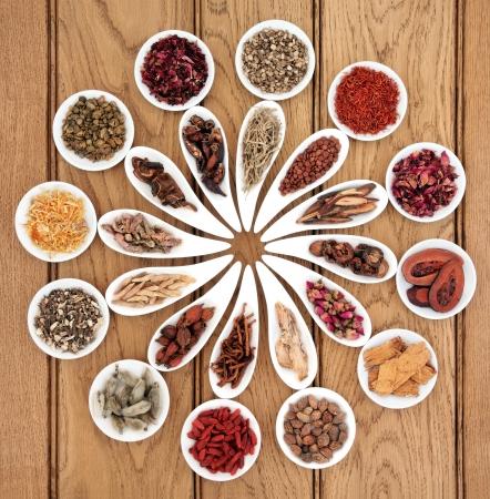オーク背景上の白い磁器の皿で大規模な中国の漢方薬の選択 写真素材