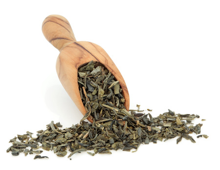 chun: Chun mee green tea leaves in an olive wood scoop over white background