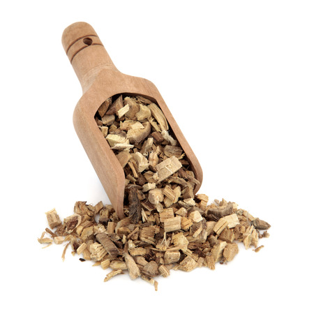 herbology: Licorice root used in chinese herbal medicine in a wooden scoop over white background  Gan cao