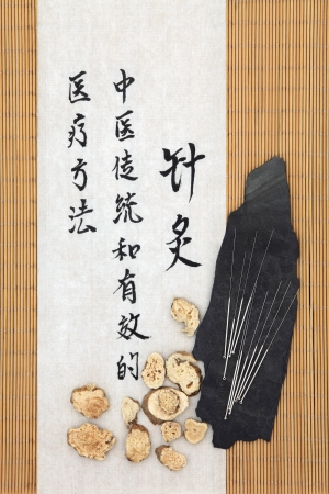 describes: Acupuncture needles with atractylodes rhizome and mandarin script on rice paper over bamboo  Bai zu  Translation describes acupuncture chinese medicine as a traditional and effective medical solution