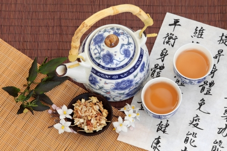 describes: Jasmine tea with flowers used in chinese herbal medicine with mandarin calligraphy on rice paper and teapot  Translation describes the medicinal functions to increase the bodys ability to maintain body and spirit health and balance energy
