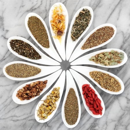 dried herbs: Herb tea selection in white porcelain dishes over marble background