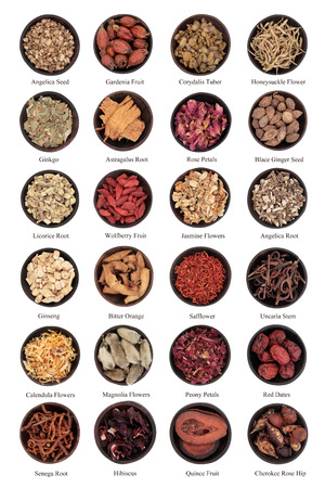 Large traditional chinese herbal medicine selection in wooden bowls isolated over white background