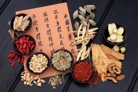 Traditional chinese herbal medicine selection with mandarin calligraphy  Translation describes the medicinal functions to increase the bodys ability to maintain body and spirit health and balance energy  photo