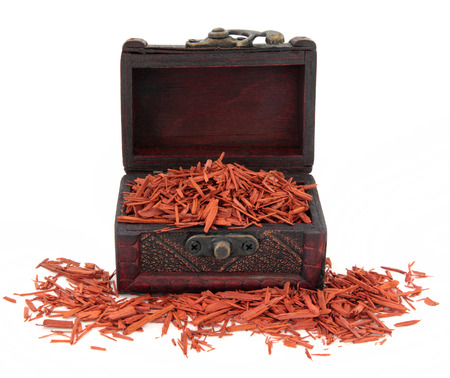 Sandalwood in an old wooden box over white background