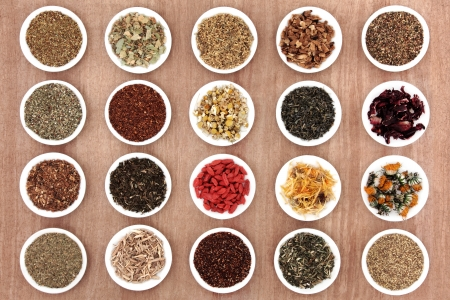 Large herbal tea selection in white porcelain dishes over papyrus background   photo