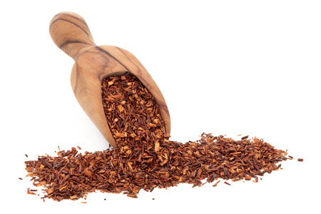 Rooibos herbal tea in an olive wood scoop over white background  photo