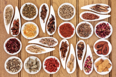 traditional remedy: Large chinese herbal medicine selection in white porcelain dishes over oak background