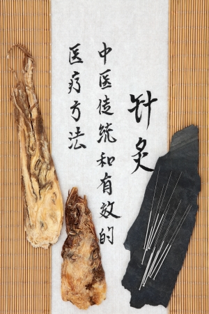 Acupuncture needles with angelica herb root and mandarin script on rice paper over bamboo  Dang gui pian  Translation describes acupuncture chinese medicine as a traditional and effective medical solution