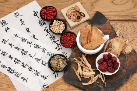 alternative medicine: Traditional chinese herbal medicine selection with mandarin calligraphy on rice paper over oak  Translation describes the medicinal functions to increase the bodys ability to maintain body and spirit health and balance energy