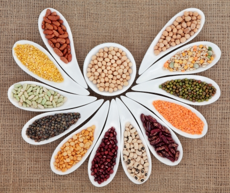 pulses: Dried pulses selection in white porcelain dishes over hessian background