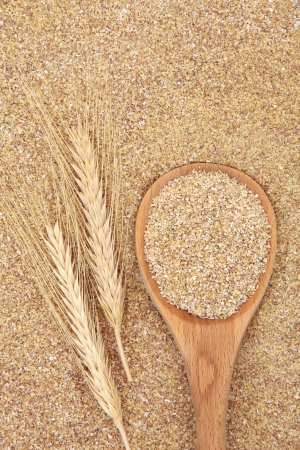 Wheatgerm in a wooden spoon with wheat ears forming a textured background  photo