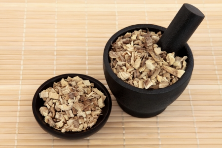 licorice: Licorice root used in chinese herbal medicine in a black stone mortar with pestle and bowl over bamboo  Gan cao  Glycyrrhiza glabra