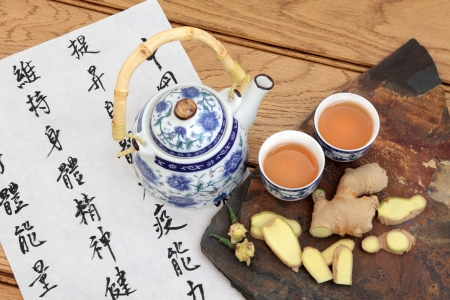 ginger health:  Ginger tea used in chinese herbal medicine with mandarin calligraphy on rice paper and teapot   Translation describes the medicinal functions to increase the bodys ability to maintain body and spirit health and balance energy  Stock Photo