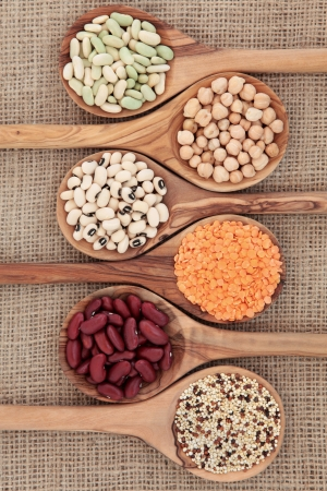pulses: Dried pulses selection in olive wood spoons over hessian background