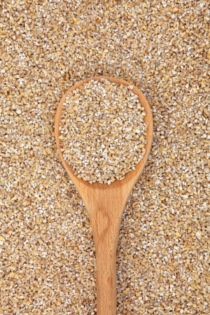 pinhead: Pinhead oatmeal in a wooden spoon and forming a background  Stock Photo