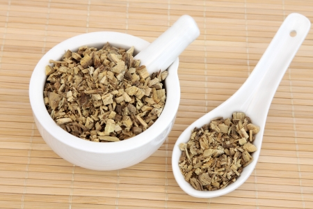 licorice: Licorice herb root used in chinese herbal medicine in a mortar with pestle and spoon  Gan cao  Glycyrrhiza glabra