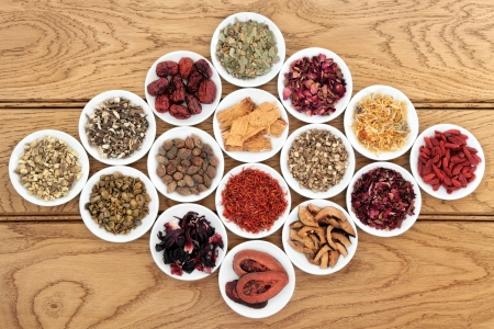 Chinese herbal medicine selection in white porcelain dishes over oak background  Stock Photo