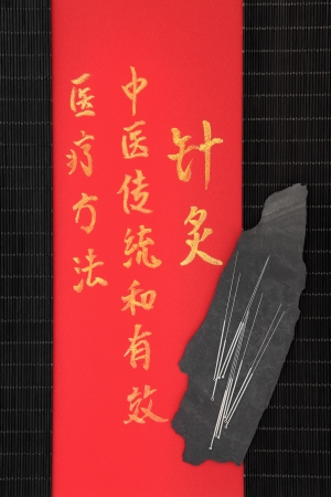 describes: Acupuncture needles and mandarin script on rice paper over bamboo  Translation describes acupuncture chinese medicine as a traditional and effective medical solution