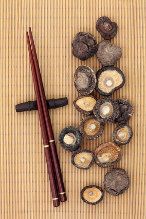 Shiitake mushrooms with chopsticks over bamboo  photo