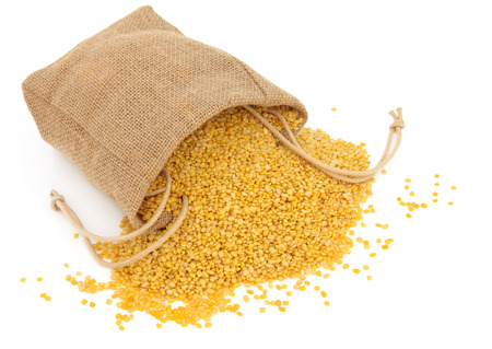 Mung dahl dried food ingredient in a hessian bag over white background