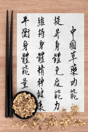 Licorice root herb chinese herbal medicine with mandarin script calligraphy on rice paper  Gan cao  Translation describes the functions to increase the bodys ability to maintain body and spirit health and to balance energy  photo
