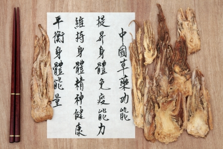 describes: Angelica root chinese herbal medicine with mandarin script calligraphy over rice paper and papyrus  Dang gui  Translation describes the functions to increase the bodys ability to maintain body and spirit health and to balance energy