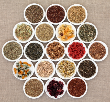 dried herbs: Herbal tea selection  in white porcelain dishes over hessian background