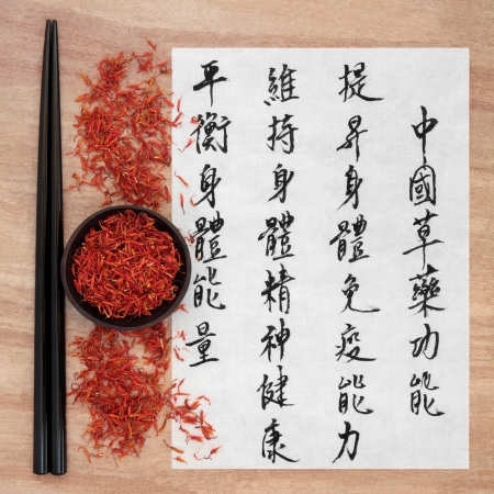 Safflower flower chinese herbal medicine with mandarin script calligraphy  Hong hua  Translation describes the functions to increase the bodys ability to maintain body and spirit health and to balance energy  photo