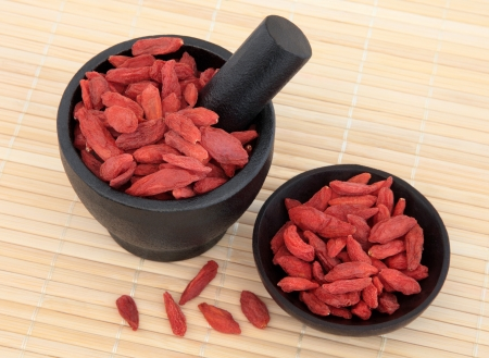 herbal remedy: Wolfberry fruit used in chinese herbal medicine in a mortar with pestle and bowl over bamboo  Gou qi zi