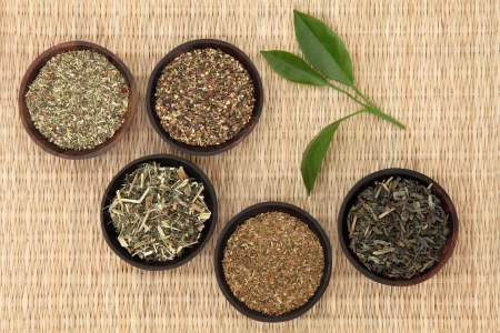 herbal remedy: Green tea leaf selection of ginseng, jasmine, st johns wort, nettle and peppermint over wicker background