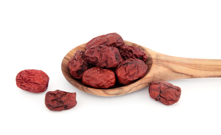 jujube fruits: Jujube, red dates used in chinese herbal medicine in a wooden spoon over white