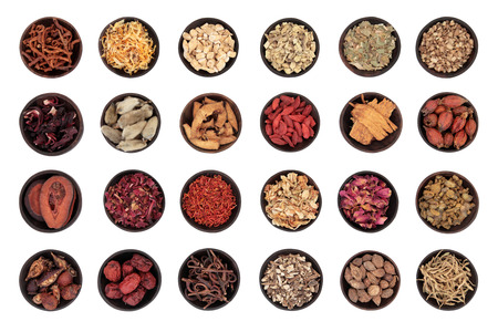 Traditional chinese herbal medicine in wooden bowls isolated over white  Imagens