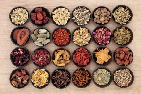Large chinese herbal medicine selection in wooden bowls over papyrus background  Stock Photo