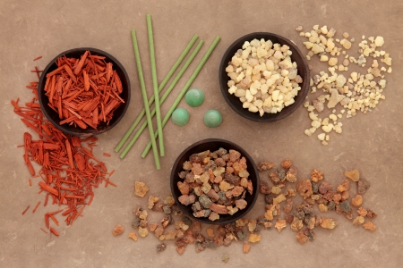 myrrh: Frankincense, myrrh, sandalwood and incense sticks and cones over lokta paper background