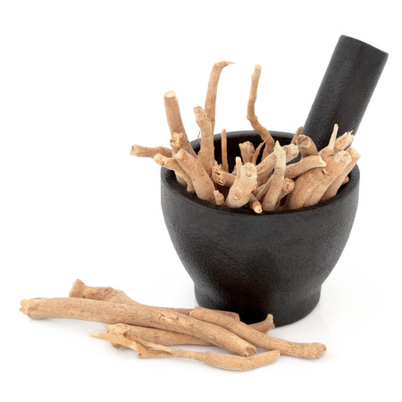 Ginseng herbal medicine in a mortar with pestle over white background  Zdjęcie Seryjne